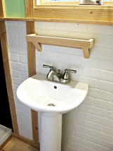 Pedestal bathroom sink and faux brick wall.