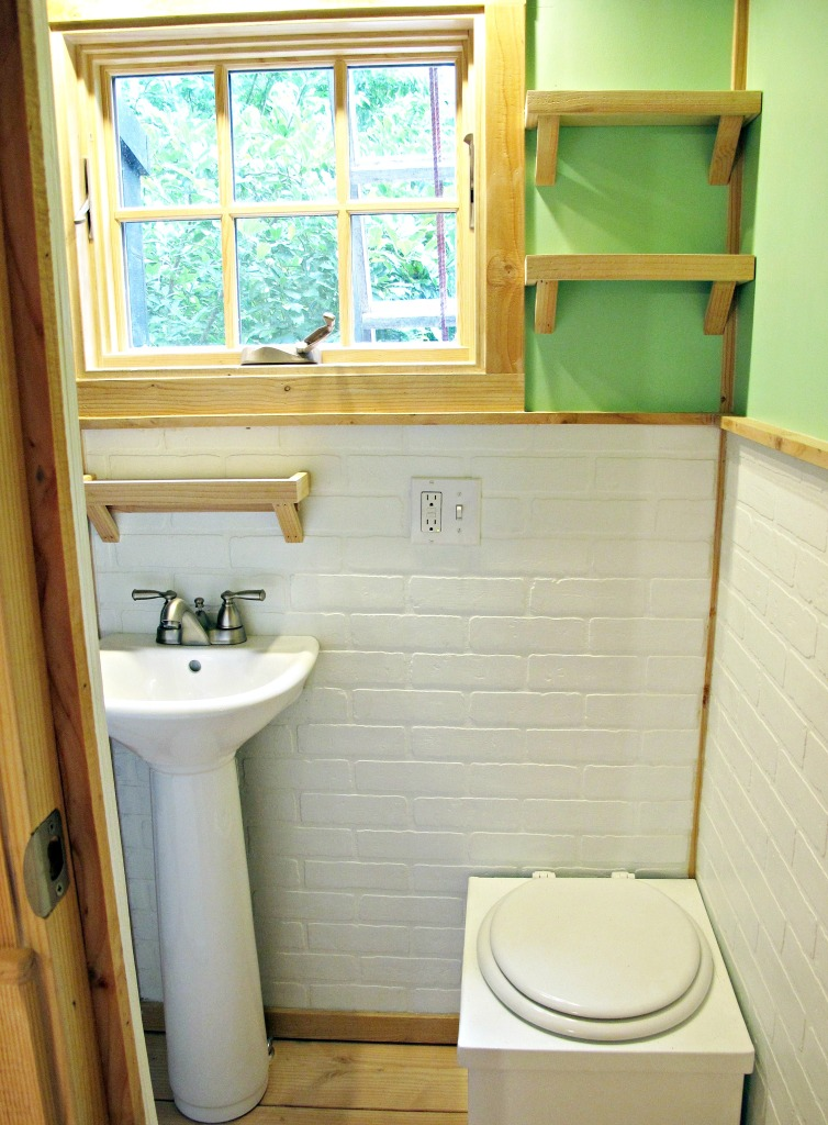 Partial view of bathroom: compost toilet and small pedestal sink and open shelves.