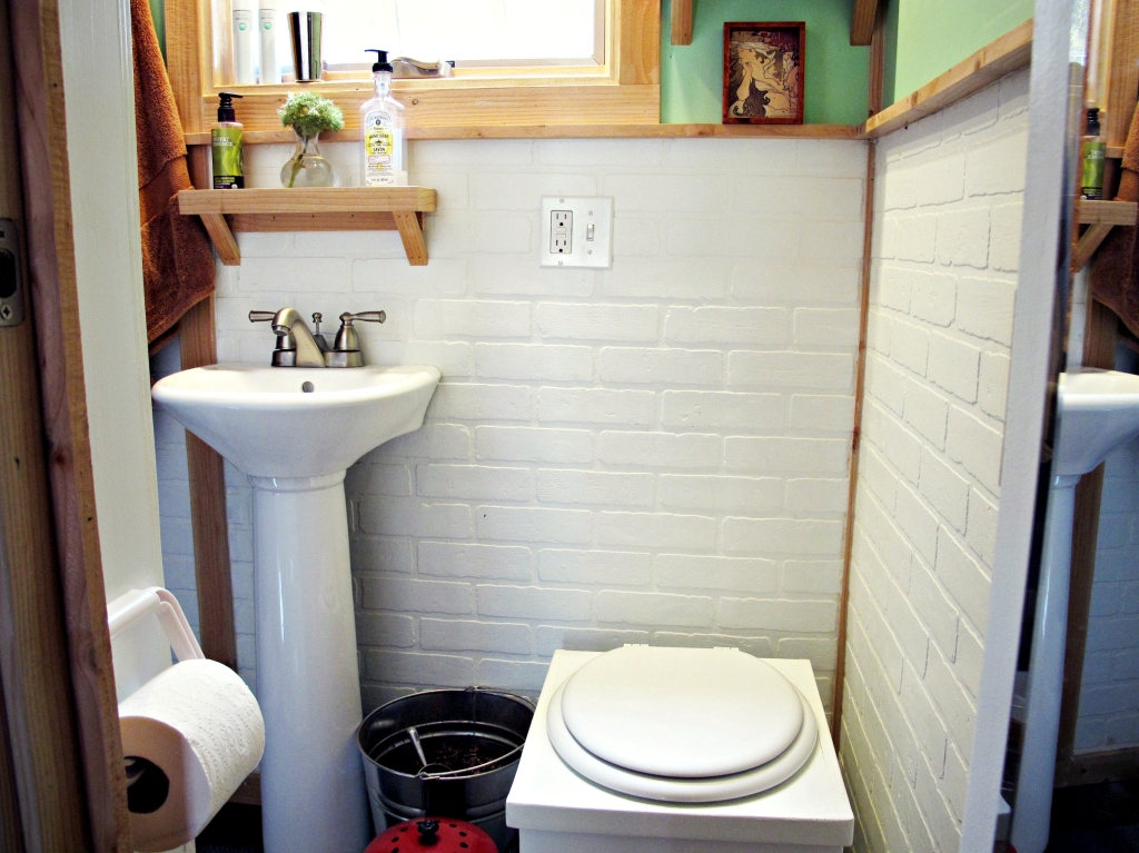 Our bathroom: small pedestal sink, bucket toilet, and more white faux-brick.