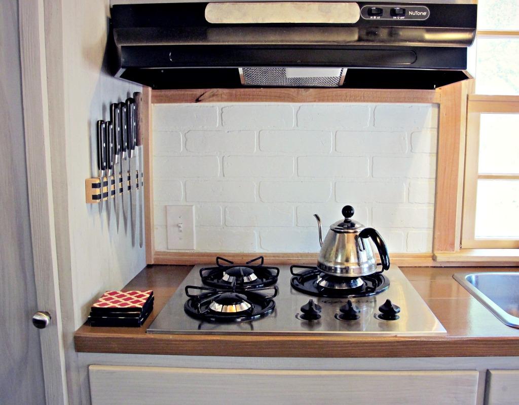 Princess three-burner gas cooktop and white faux-brick backsplash.
